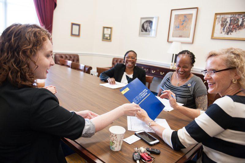 NCCS CPAT Member hands a congressional staffer a leave-behind packet.